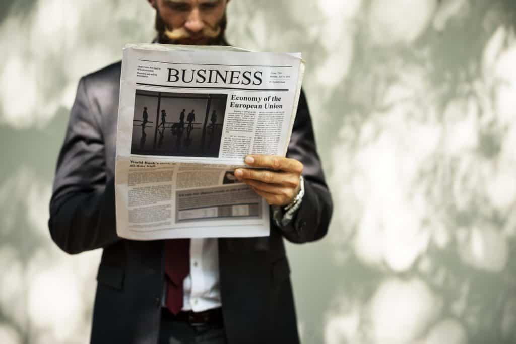 junger Geschäftsmann mit Hipster-Bart, Anzug und Krawatte geht im Park spazieren und liest den Wirtschaftsteil einer Zeitung